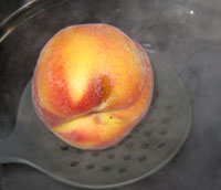We dip the peaches into boiling (simmering) water, we put in about 6 peaches at a time for approximately 1 minute, then immediately remove the peaches and put them in cold water to cool the peaches down, or you will cook them.